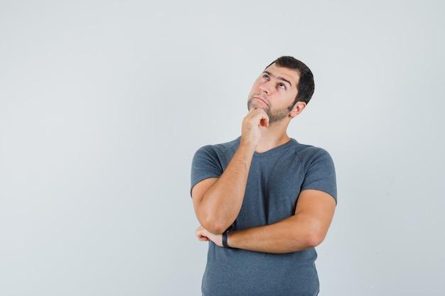 Jeune homme portant le menton sur place en t-shirt gris et à l'hésitant