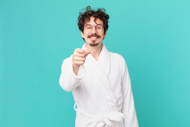 Jeune homme portant un peignoir pointant vers la caméra vous choisissant
