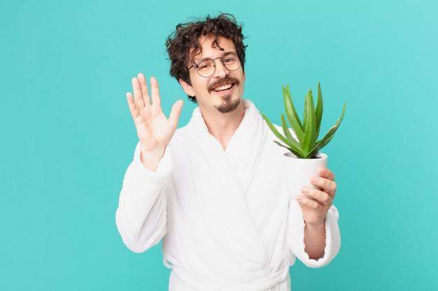 Jeune homme portant un peignoir souriant joyeusement, agitant la main, vous accueillant et vous saluant