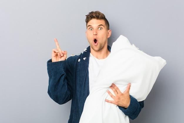 Jeune homme portant pijama tenant un oreiller ayant une excellente idée, concept de créativité.