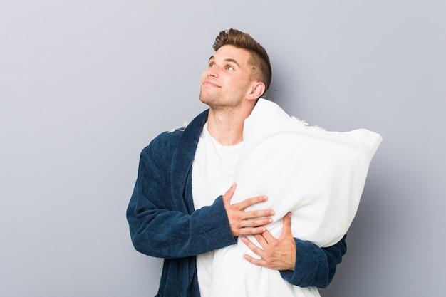 Jeune homme portant un pijama tenant un oreiller à côté avec une expression douteuse et sceptique.