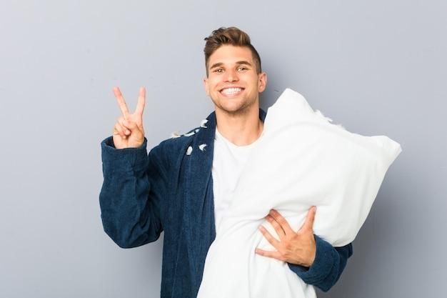 Jeune homme portant pijama tenant un oreiller montrant le numéro deux avec les doigts.