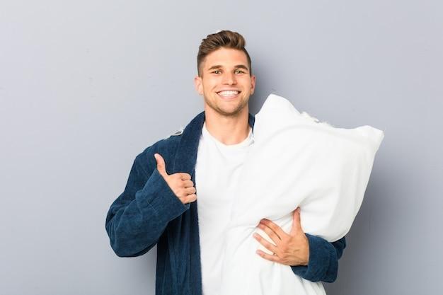 Jeune homme portant un pijama tenant un oreiller souriant et levant le pouce vers le haut