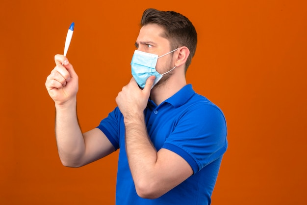 Jeune homme portant un polo bleu dans un masque de protection médicale à la recherche de thermomètre numérique à la main nerveux et inquiet debout avec la main sur le menton sur un mur orange isolé