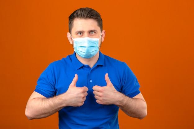 Jeune homme portant un polo bleu en masque de protection médicale montrant les pouces vers le haut sur un mur orange isolé