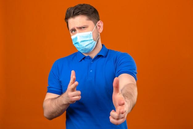 Jeune homme portant un polo bleu en masque de protection médicale pointant avec les doigts vers la caméra avec une expression sceptique debout sur un mur orange isolé