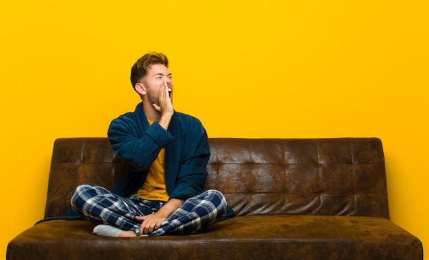 Jeune homme portant un pyjama de profil, l'air heureux et excité, criant et appelant la surface sur le côté. assis sur un canapé