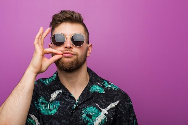 Jeune homme portant un regard de vacances avec les doigts sur les lèvres en gardant un secret