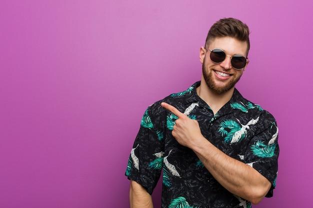 Jeune homme portant un regard de vacances souriant et pointant de côté, montrant quelque chose à un espace vide.