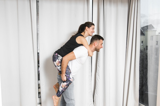 Jeune homme portant sa copine sur le dos devant le rideau
