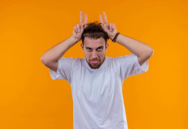 Jeune homme portant un t-shirt blanc montrant la langue et les oreilles de lapin geste sur mur orange isolé