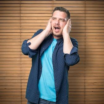Jeune homme portant une tenue bleue. couvrant ses oreilles.