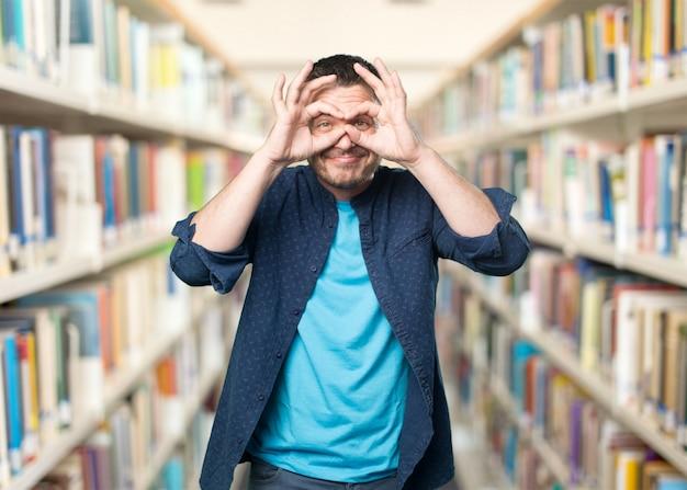 Jeune homme portant une tenue bleue. faire des lunettes geste.