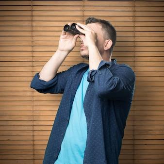 Jeune homme portant une tenue bleue. il utilise des jumelles
