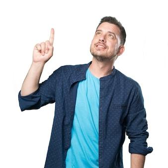 Jeune homme portant une tenue bleue. pointant vers le haut avec son doigt.