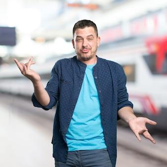 Jeune homme portant une tenue bleue. regarder drôle.
