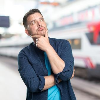 Jeune homme portant une tenue bleue. regarder thoughful.
