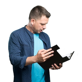 Jeune homme portant une tenue bleue. tenir un dossier noir. regardant