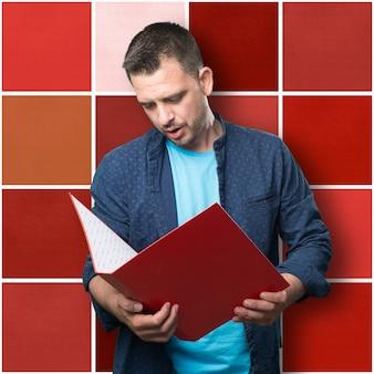 Jeune homme portant une tenue bleue. tenir un dossier rouge.