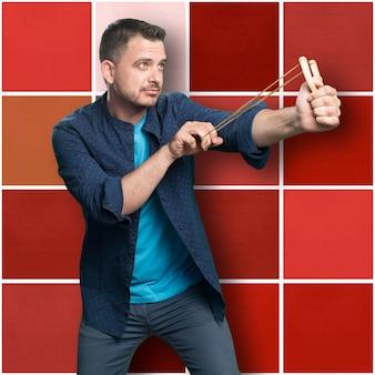 Jeune homme portant une tenue bleue. l'utilisation d'un lance-pierre. pointong à