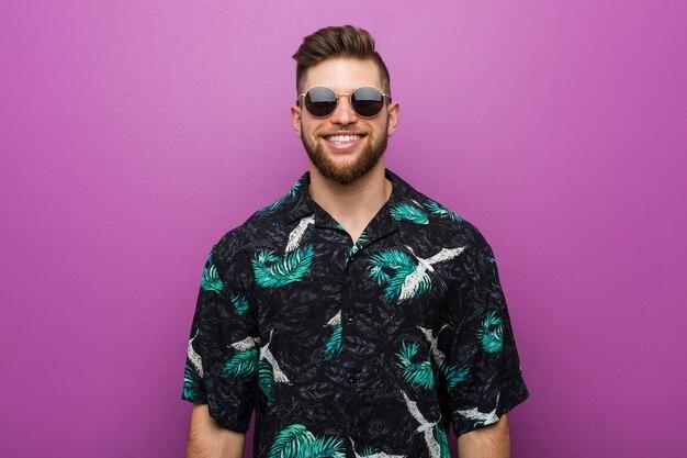 Jeune homme portant des vacances a l'air heureux, souriant et gai.