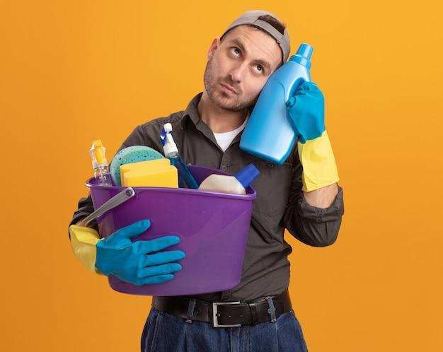 Jeune homme portant des vêtements décontractés et une casquette dans des gants en caoutchouc tenant un seau avec des outils de nettoyage et des fournitures de nettoyage de bouteille à la perplexité debout sur le mur orange