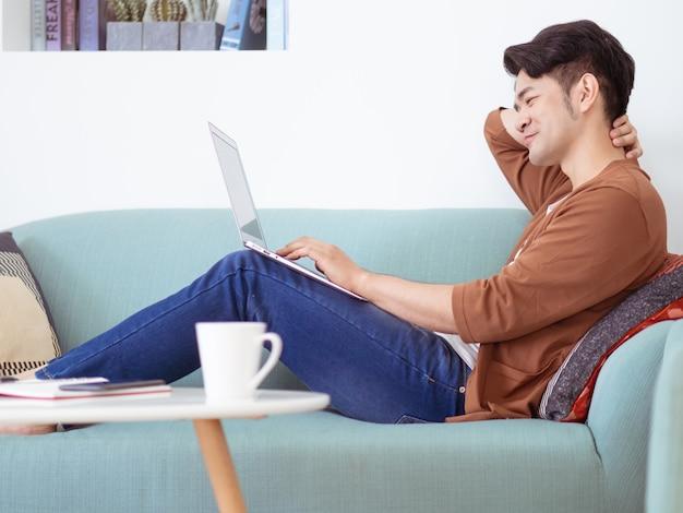 Jeune homme portant des vêtements décontractés et utilisant un ordinateur portable