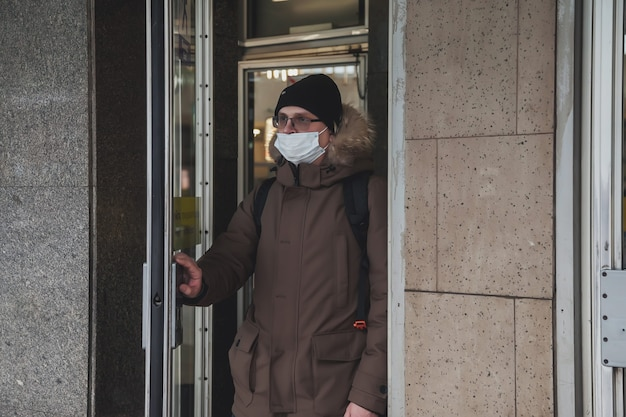 Jeune homme portant des vêtements d'hiver décontractés avec des lunettes et un masque médical à la sortie de la station de métro