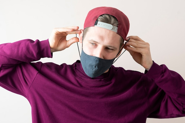 Un jeune homme porte le masque textile noir pour se protéger du virus covid-19, des vêtements décontractés