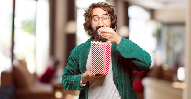 Jeune homme, porter, nuit, peignoir, avec, popcorns, seau