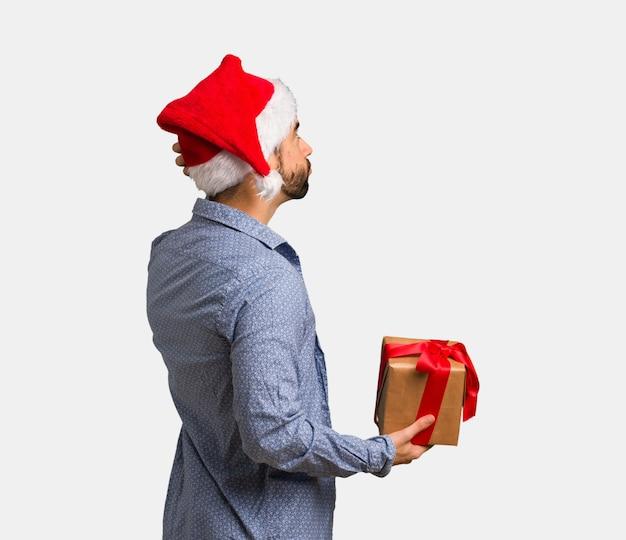 Jeune homme, porter, santa hat, par derrière, penser quelque chose