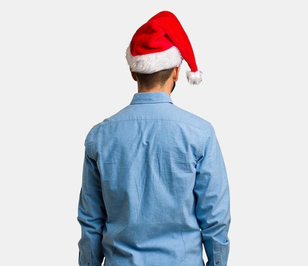 Jeune homme, porter, santa hat, par-derrière, regarder dos