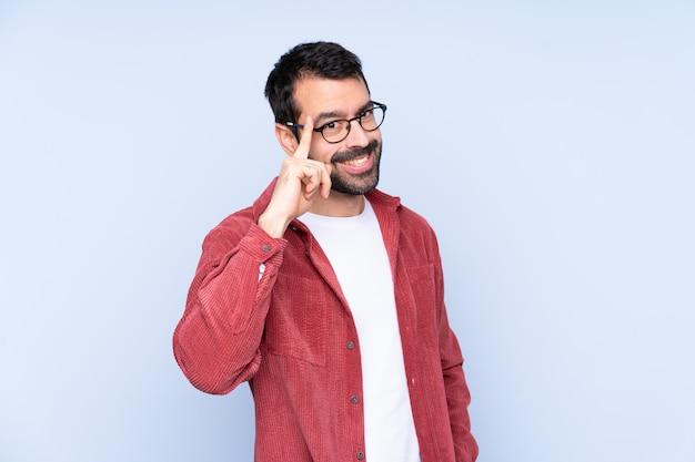 Jeune homme, porter, veste velours côtelé, sur, mur bleu, à, lunettes, et, heureux