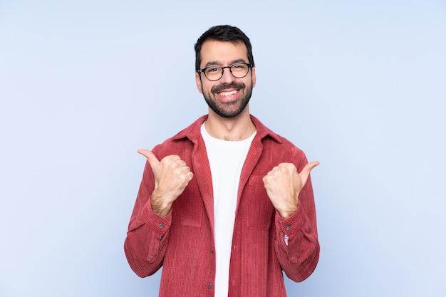 Jeune homme, porter, veste velours côtelé, sur, mur bleu, à, pouces haut, geste, et, sourire
