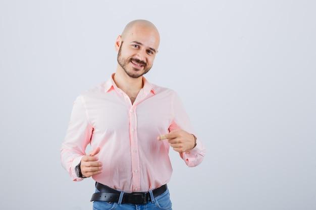 Jeune homme posant comme tenant quelque chose tout en le pointant en chemise rose, en jean et l'air amusé, vue de face.