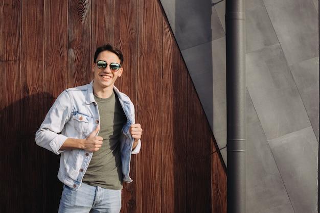 Jeune homme posant dans ses lunettes de soleil à côté du mur