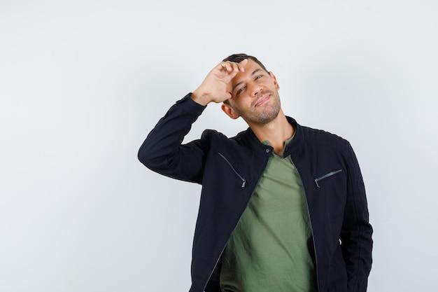 Jeune homme posant debout en t-shirt, veste et l'air joyeux. vue de face.