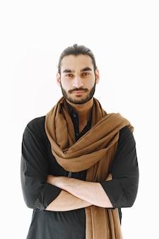 Jeune homme posant avec désinvolture sur un mur blanc. studio, isolé.