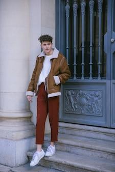 Jeune homme posant devant la porte