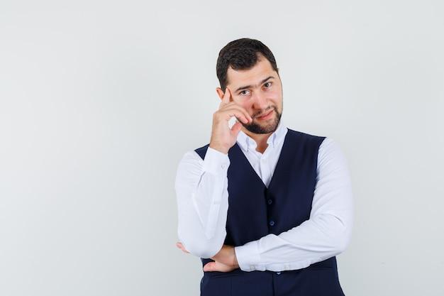 Jeune homme posant avec le doigt sur les tempes en chemise et gilet et à l'élégant