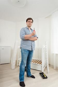 Jeune homme posant avec des outils au lit bébé démonté