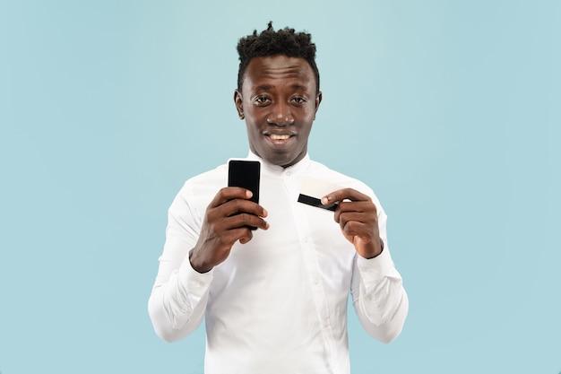Jeune homme posant avec smartphone isolé sur mur bleu studio