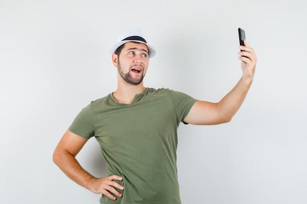 Jeune homme posant tout en prenant selfie en t-shirt vert et chapeau et à la bonne humeur