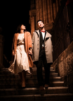 Jeune homme positif, main dans la main avec une femme élégante heureuse sur les marches