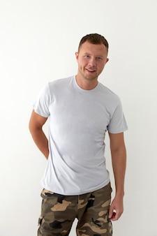 Jeune homme positif en pantalon militaire kaki main derrière et t-shirt gris debout sur fond blanc et regardant la caméra