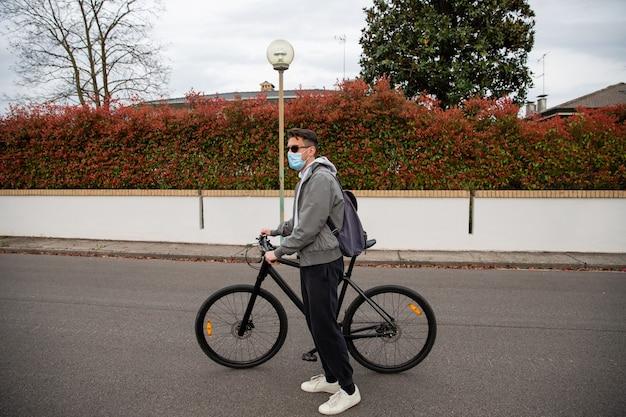 Un jeune homme pousse son vélo avec ses mains il se tient dans une rue et porte un masque chirurgical