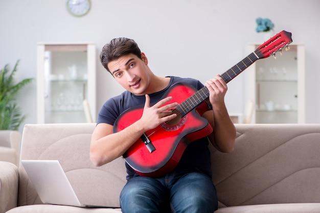 Jeune homme pratiquant la guitare à la maison