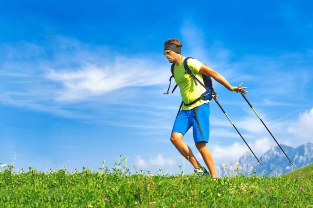 Jeune homme pratiquant la marche nordique dans la nature