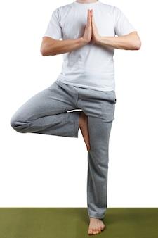 Jeune homme pratiquant le yoga isolé sur fond blanc.