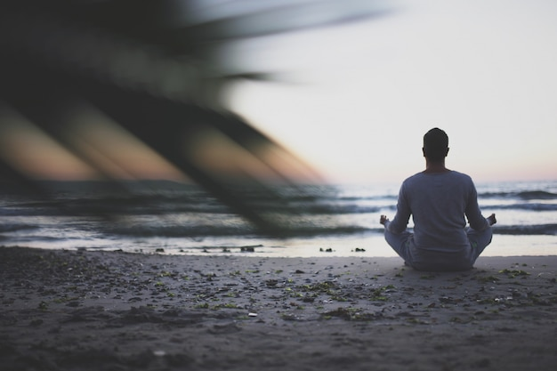Jeune homme pratique le yoga sur la plage au coucher du soleil.